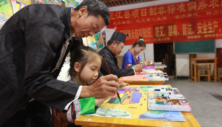 7月12日,三江农民画传承人杨共国老师在教小朋友作画。