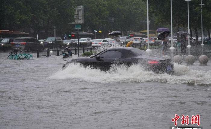7月20日,河南郑州,车辆经过积水路段。近日,郑州连遭暴雨袭击,持续强降雨导致部分街道积水严重。 中新社记者 阚力 摄